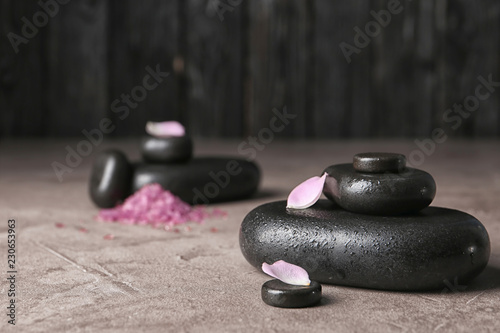 Leinwanddruck Bild Spa stones and flower petals on table. Space for text