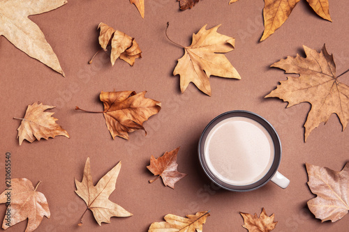 Leinwanddruck Bild Flat lay composition with hot cozy drink and autumn leaves on color background