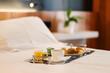 Plateau de petit-déjeuner contenant du café, jus d'orange, croissant et yaourt posé sur le lit d'une chambre d'hôtel recouvert d'un drap blanc avec une plante verte en arrière plan.