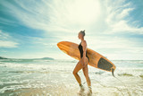 Beautiful sexy and sporty girl surfer walks with a board on the beach at sunrise. Active lifestyle and recreation - 230659143