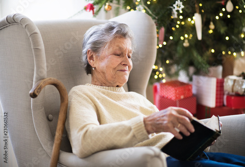 Leinwandbild Motiv A lonely senior woman reading Bible at home at Christmas time.