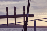 Vintage toned picture of an old sailing ship rigging elements silhouettes at sunset, selective focus. - 230677198