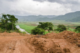 River and dirt road with mountains and lush vegetation, Bamenda Ring Road , Cameroon, Africa. - 230678387