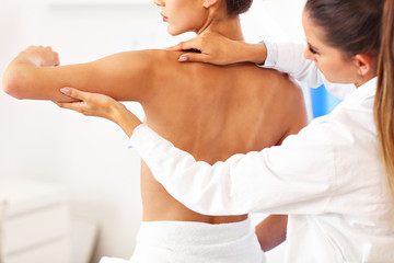 Female physiotherapist helping a patient with back problems in clinic