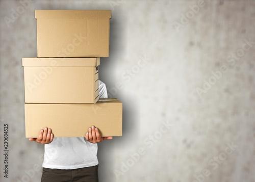 Leinwanddruck Bild Man with cardboard boxes on brick background