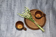 Clay coffee cups and ceramic round dish with bouquet of white forest lily of the valley on dark concrete background