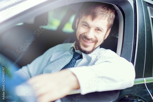 Foto Murales Young happy man in car smiling - concept of buying car