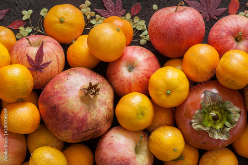 Foto Murales Italian autumn harvest: garnet, mandarins, persimmons, apples.