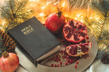 Fruits and vegetables for harvesting. Still life - bible and pomegranate on an iron plate in the branches of the Christmas tree