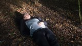 Young man lying down and resting on a patch of leaves in a sunny autumn forest - 230727979