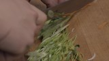 Close-up of a cook slicing scallions in a kitchen of a restaurant - 230737155