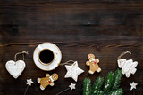 New Year gingerbread cookies. Gingerbread man near coffee, spruce branch, festive decoration on dark wooden background top view copy space - 230737987