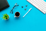 Office desk of creative person or hipster.Cute workplace. Keyboard and glasses near coffee, notebook, green room plant and stationery on blue, turquoise background top view copy space - 230738383