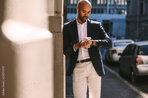 Poster Young businessman checking time