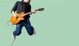 Male Guitarist playing music on grey wall - 230757547