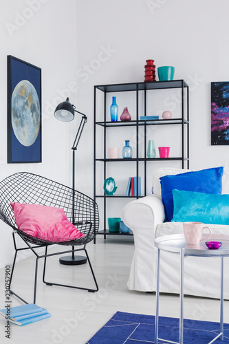 Vertical view of stylish armchair with pink pillow in modern living room interior with white sofa nd moon graphic on the wall - 230757900