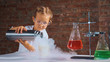 Cute child researcher is conducting an experiment with liquid nitrogen