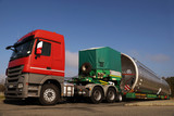 A view of a truck, a low-loader semi-trailer and an oversized cargo in the parking lot. - 230773349