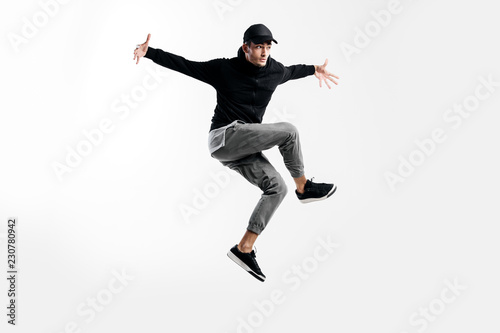Handsome young dancer wearing a black sweatshirt, gray pants and a cap is dancing breakdance