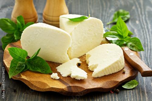 cheese brynza  and garlic on a cutting board. - 230784177