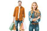 beautiful smiling woman posing with crossed arms while her boyfriend standing behind with shopping bags isolated on white - 230785960