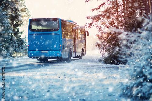 Leinwandbild Motiv bus on winter road through coniferous forest