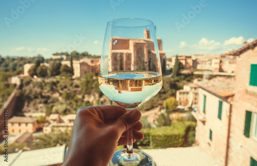 Historical church Basilica of San Domenico in reflection of a glass of wine. Ancient city Siena, Italy