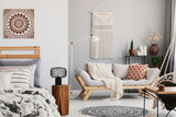 Small open space flat interior with beige sofa with cushion, macrame on the wall, rack with candles and plants and bed with pillows - 230828908