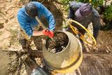 Workers pour concrete solution at a construction site - 230839564