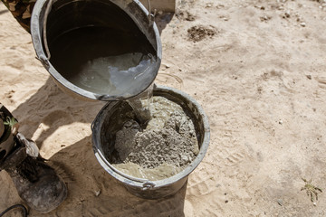 Mixing of concrete in a bucket at a construction site