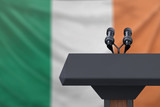 Podium lectern with two microphones and Irish flag in background