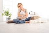 home concepts, young woman hugging a big comfortable cushions, sitting on the wooden floor of a modern living room, copy space template - 230854953