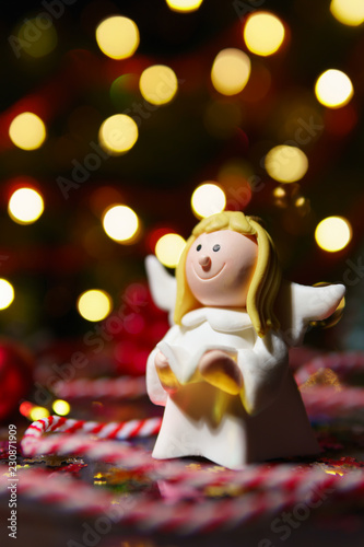Small toy angel in lights of garland - 230871909
