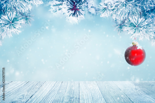 Christmas background with red ornament and falling snow on pine tree branches - 230879758