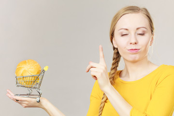 Woman holding shopping cart with bread