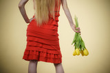 woman with yellow tulips bunch, back view - 230890522