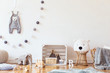 Stylish scandinavian child room with mock up photo poster frame on the pattern wall, boxes, teddy bear and toys.Cute modern interior of playroom with white walls, wooden accessories and colorful toys.