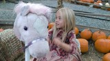 Young girl riding pretend horse at pumpkin patch - 230891961