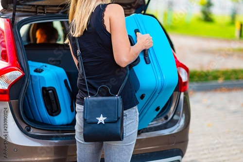 Foto Murales Young woman loading two blue plastic suitcases to car trunk.