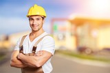 Young builder in hardhat on blurred construction materials store - 230904140