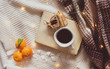 flat lay or top view of a book, cup of coffee, chocolates, mandarin oranges and yellow lights on white and checkered woolen scarf background. Autumn or winter holiday season coffee or breakfast.