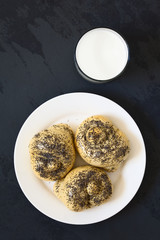 Homemade poppy seed bread rolls on plate with a glass of milk, photographed overhead on slate with natural light (Selective Focus, Focus on the top of the rolls)