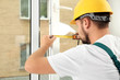 Leinwanddruck Bild - Construction worker installing new window in house