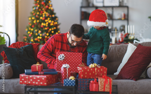 family father and child son open presents on Christmas morning © JenkoAtaman