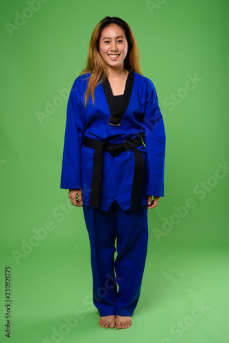 Young Asian woman wearing blue karate Gi against green backgroun