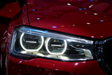 Closeup headlights of modern red car during turn on light in night.