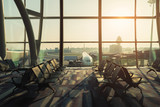 Empty chairs in the departure hall at airport with airplane taking off at sunset. Travel and transportation in airport concepts. - 230925178