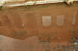 The Colosseum is reflected in a puddle with a brown background, unusual foreshortening sights of Rome Italy