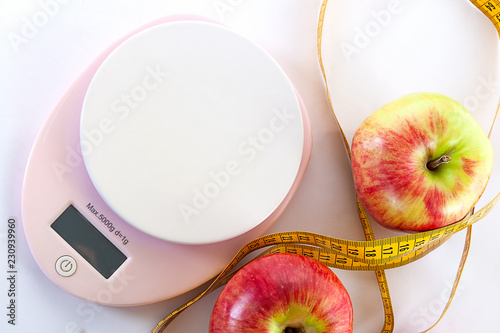 Leinwandbild Motiv Diet concept. Apples and table top kitchen scales and measuring tape lie on a white background. Top view, close-up.