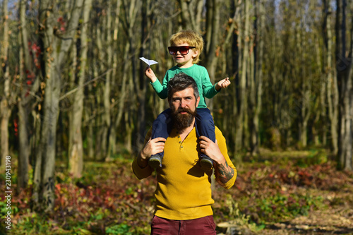 Foto Murales Happy little boy go on journey on fathers shoulder. Journey into the country. The world is yours to explore